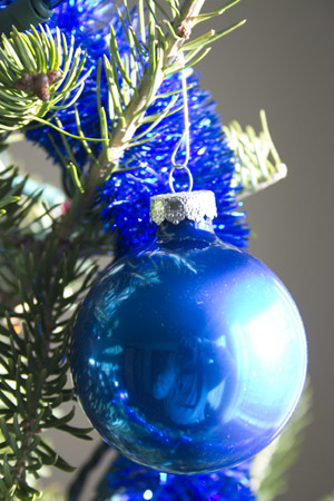 Close-up of a Christmas ornament hanging on our tree, reflecting me with camera